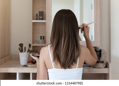 Young woman sitting and doing makeup in front of mirror in dressing room