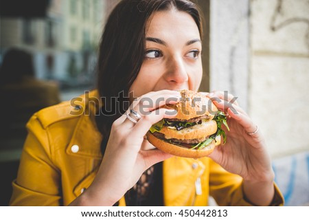Young woman sitting  eating an hamburger hand hold- hunger, food, meal concept