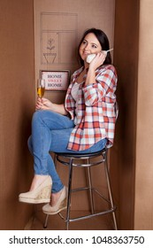 Young woman sitting in an empty box talking on the phone. Smiling brunette with a glass of wine