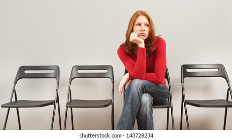 A young woman sitting in an empty waiting room and looking bored.
