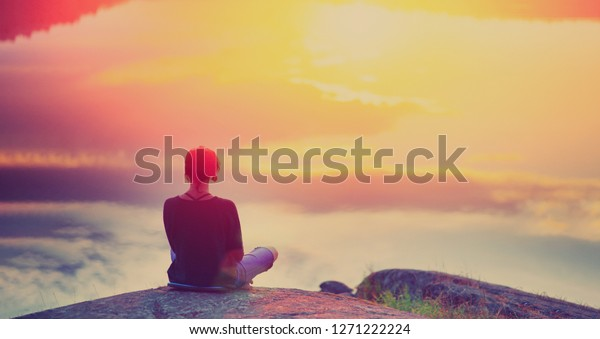 Young woman sitting enjoying peaceful moment of beautiful colorful sunset. In the reflection of the lake water sees clouds and sun. Vintage mood, concepts of winner, freedom, happiness.