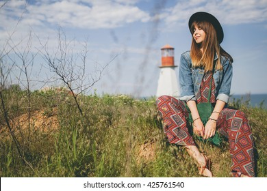 young woman sitting in field, nature background, lighthouse, hipster style, bohemian outfit, printed overall, denim jacket, black hat, smiling, happy, summer, sunny, stylish accessories