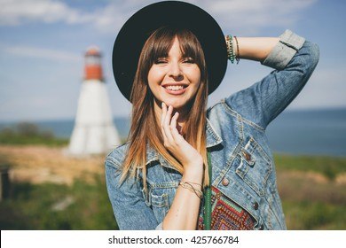 young woman sitting in field, nature background, lighthouse, hipster style, bohemian outfit, denim jacket, black hat, smiling, happy, summer, sunny, stylish accessories, bracelets, hands