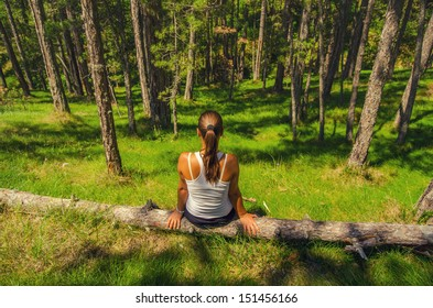 Young woman sitting in the forest on sunny summer day.