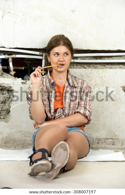 young woman sitting in the front of demolished wall, planning repairing pipeline