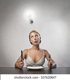 Young woman sitting in front of a dish at lunchtime with light bulb over her head