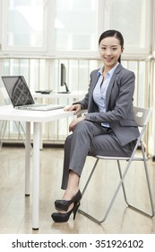 Young woman sitting in front of laptop