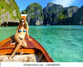 Young woman sitting at the front of longtail boat in Maya Bay on Phi Phi Leh Island, Krabi Province, Thailand. This island is part of Mu Ko Phi Phi National Park.