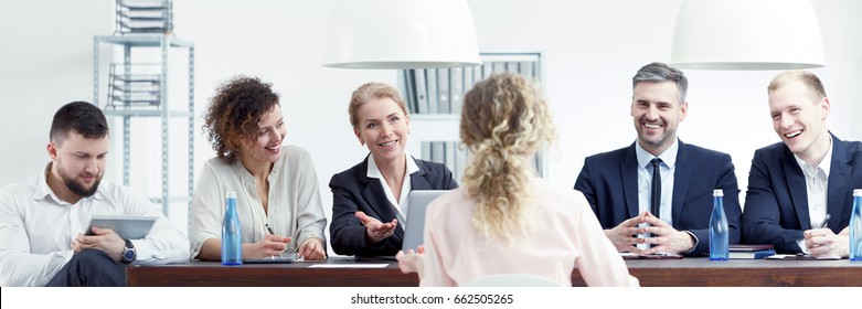 Young woman sitting in front of staff during job interview