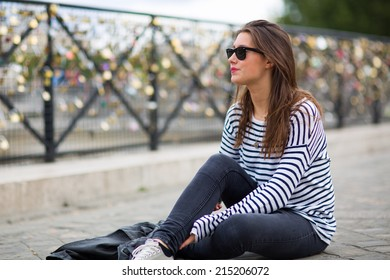 Young woman sitting in front of thousands of locks hung up at the side of a bridge in Paris, capital of France, as a sign of eternal love