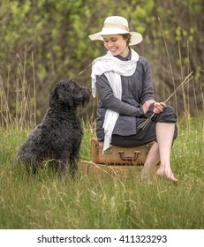 young woman sitting in the grassy outdoors with her black curly haired dog.