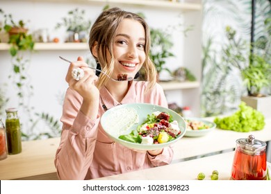 Young woman sitting with healthy food in the beautiful interior with green flowers on the background