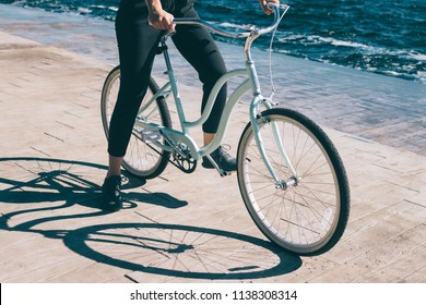 Young woman sitting at her cruiser bicycle near blue sea. Close-up female standing on the wooden embankment resting and holding handlebars of her vintage bike.
