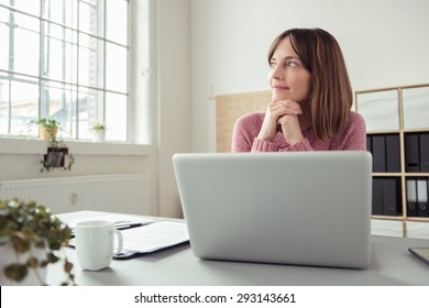 Young woman sitting at her desk in front of a gray laptop while daydreaming of nice memories or future in a modern bright office with large window