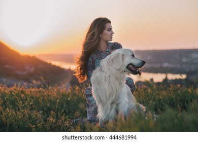 young woman sitting with her dog enjoying sunset