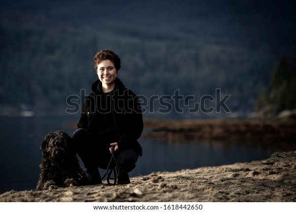 Young woman sitting with her dog on a sandy beach by the lake.