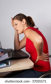Young woman sitting at her laptop with a lot of work in front of her. She has a pain in her neck / back.