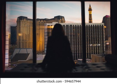 Young woman sitting in a hotel room and looking at beautiful sunset in a big city downtown