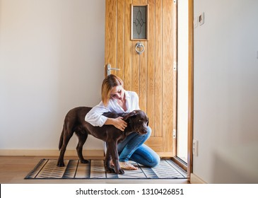 A young woman sitting indoors by the door on the floor at home, playing with a dog.