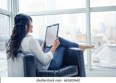 Young woman sitting indoors, in chair using digital tablet, day. young adult arabic pretty 20 years old