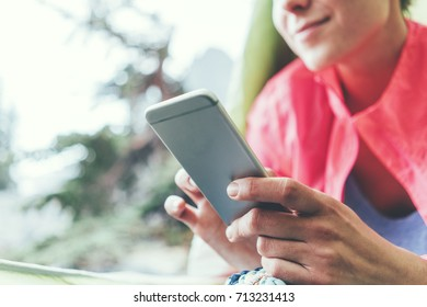 Young woman sitting inside the tent and camping in nature wilderness. Using mobile phone and texting message. Perfect network coverage outdoors