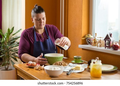 Young woman sitting in the kitchen behind a wooden table with ingredients for baking a cake. She is holding a glass of milk above a green bowl, just before pouring the milk into the bowl