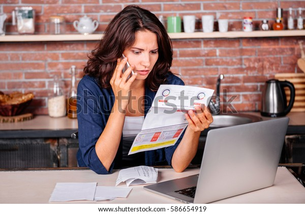 Young woman sitting in the kitchen with dissatisfied face in front of laptop holding utility bills, talking on mobile phone