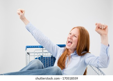 A young woman sitting in a large shopping cart and shouting for joy with her hands up in the air.