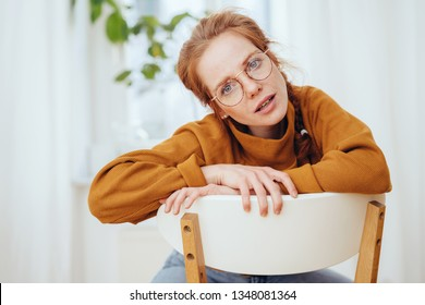 Young woman sitting leaning on the back of a kitchen chair staring at the camera in utter disbelief