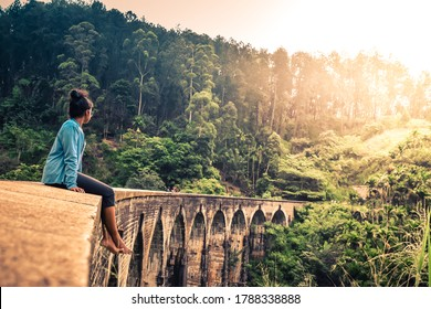 Young woman sitting leisurely on the famous nine arches bridge enjoying the beautiful view in the morning sunlight in Demodara, Ella, Sri Lanka