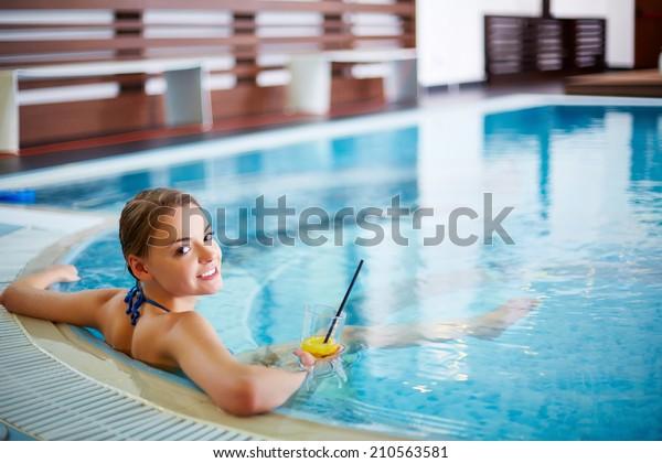 Junge Frau sitzt mit Limonade im Schwimmbad