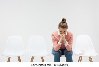 Young woman sitting in the line or queue, looking stressed, putting hands together as if she is praying with closed eyes to overcome depression