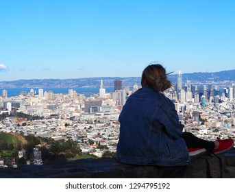 Young woman sitting and looking at the city of San Francisco and the clear blue sky, with the Transamerica Pyramid and the Salesforce tower in background