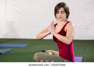 Young woman sitting in a lotos pose inddors