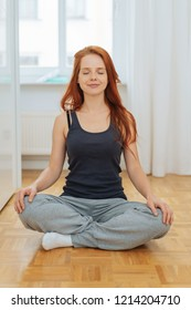 Young woman sitting meditating at home on a wooden floor sitting cross-legged with a happy smile and closed eyes