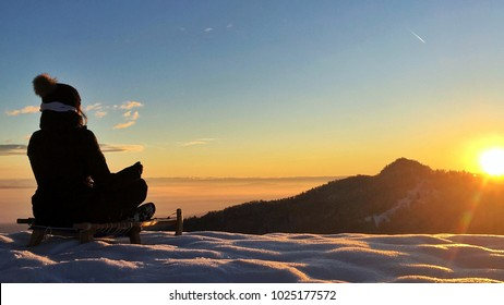 Young woman sitting and meditating on sledge looking at sunrise in winter.