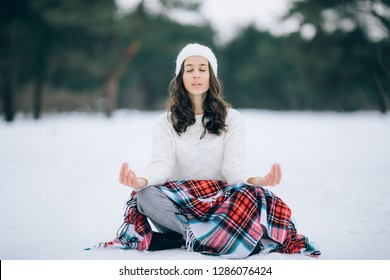 Young woman is sitting and meditating in the yoga pose on the snow during the winter walk.
