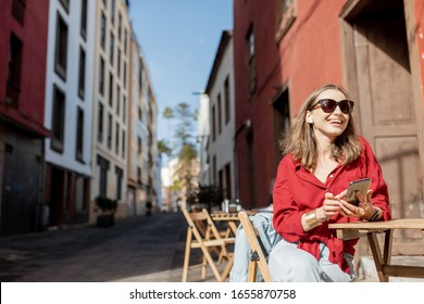 Young woman sitting with mobile phone on the cafe terrace on the old city steet during a sunny day. Street view on the old spanish town La Laguna