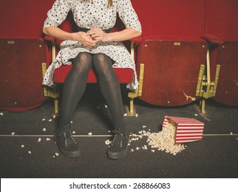 A young woman is sitting in a movie theater with a bucket of popcorn spilled on the floor in front of her