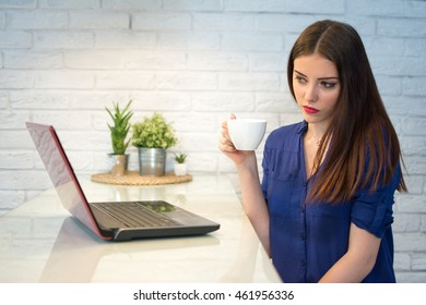 Young woman sitting near bright wall while looking at open laptop computer on table and holding white mug.