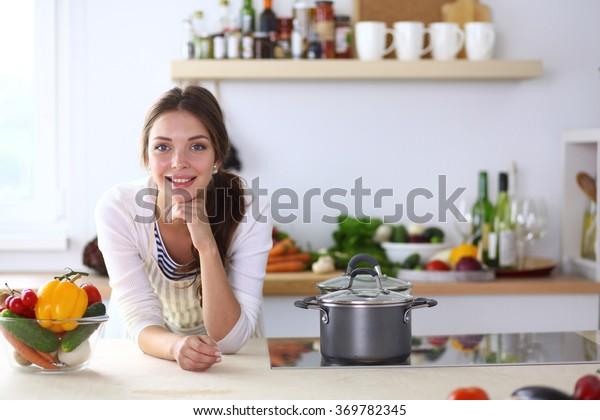 Junge Frau, die in der Küche neben dem Schreibtisch sitzt