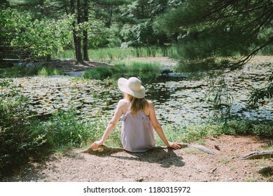 Young woman sitting near the lake full of water lillies
