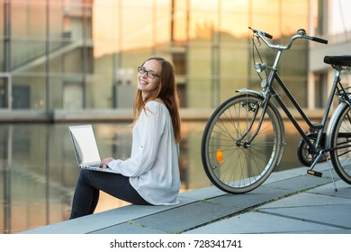 a young woman sitting near the river somewhere in the city and working with a laptop; her bicycle is standing next to her; warm golden sunlight is reflected from a glass building across the river