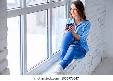 Young woman sitting near window relaxing in her living room and drinking coffee or tea. Girl in denim clothes sitting on the window sill.
