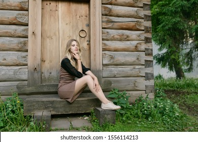 Young woman sitting near a wooden house.