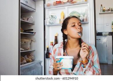 Young woman sitting next to the fridge, trying to keep diet and healthy eating. Happy to eat sweet ice cream dessert.