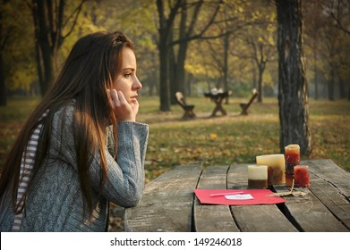 young woman sitting at old wooden table with paper and candles on it, in autumn park, pensive look