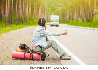 young woman  sitting on a backpack and  hitchhiking on the road