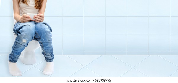 Young woman sitting on bathroom or wc toilet bowl using phone in hands .