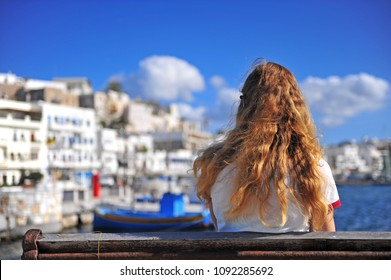 Young woman sitting on the beach at the sea, Naxos island, Greece